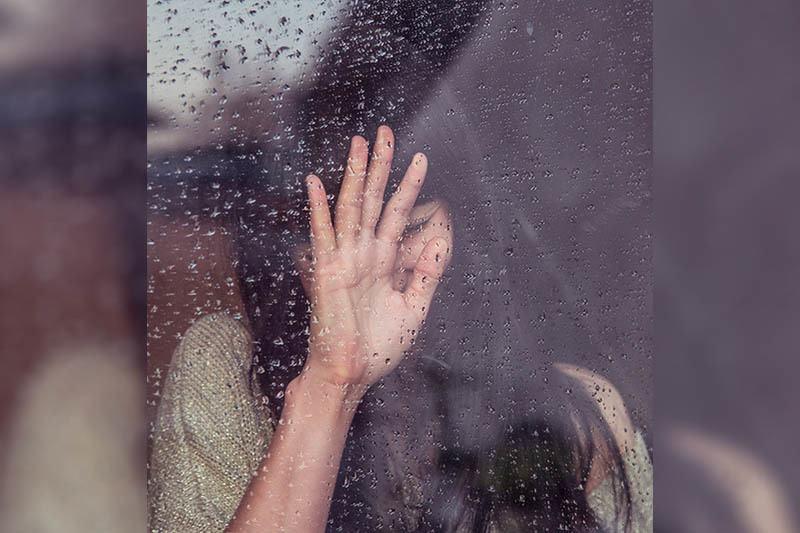eine Frau, die vor dem Regen an einem nassen Fenster stand