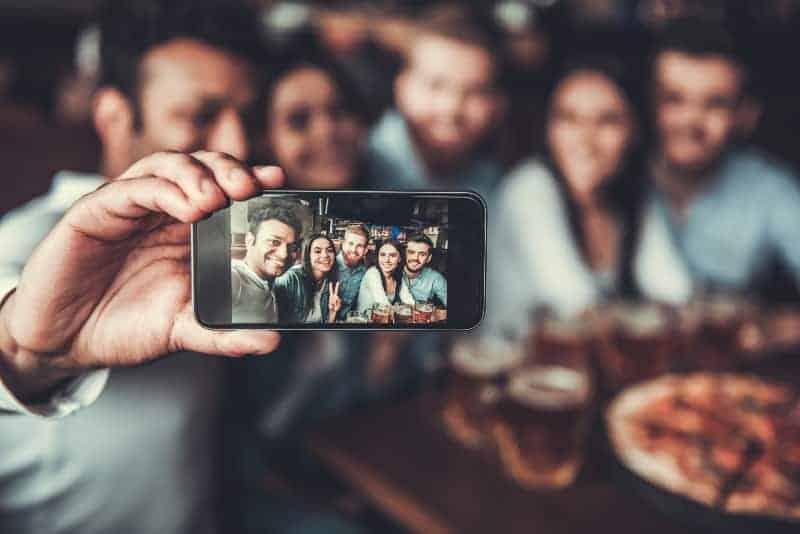 eine fröhliche Gruppe in einem Café, die ein Selfie-Foto macht