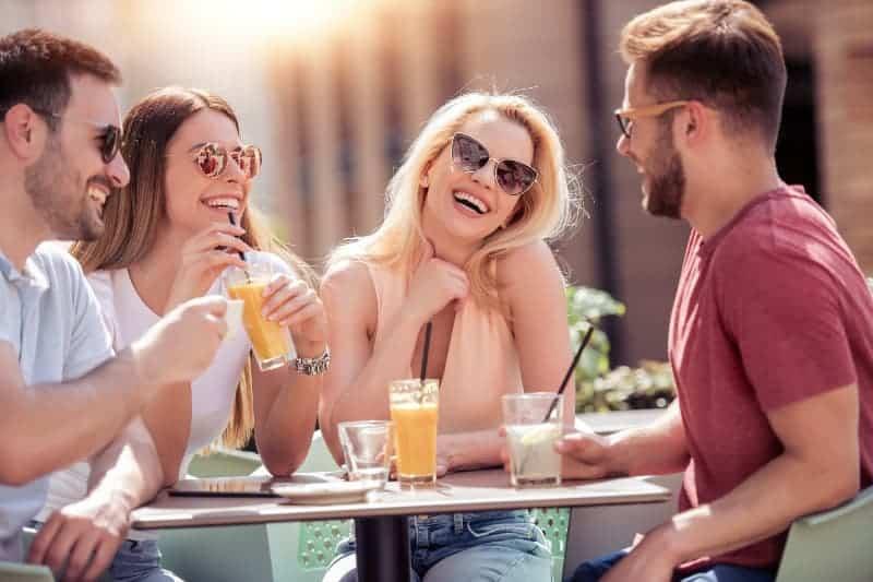 eine fröhliche Gruppe sitzt auf der Terrasse und trinkt