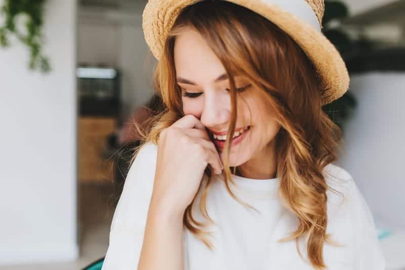 eine glückliche Frau mit einem Hut und einer Hand im Gesicht