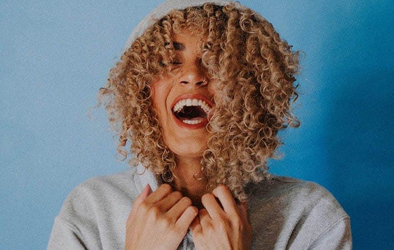 eine lächelnde Frau mit krausem Haar