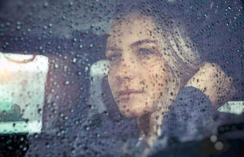 eine lächelnde Frau sitzt im Auto, während es regnet