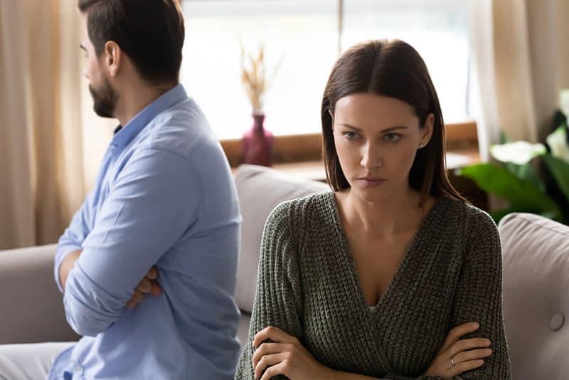 ernsthafte Frau, die getrennt von ihrem Freund sitzt