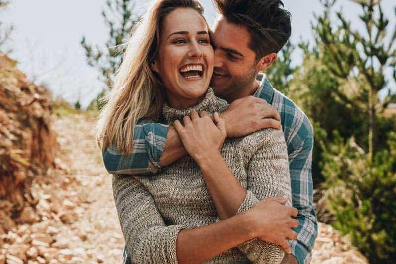 glücklicher Mann, der Frau küsst und umarmt