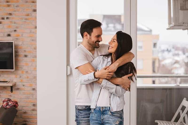 glückliches Paar, das im Haus umarmt