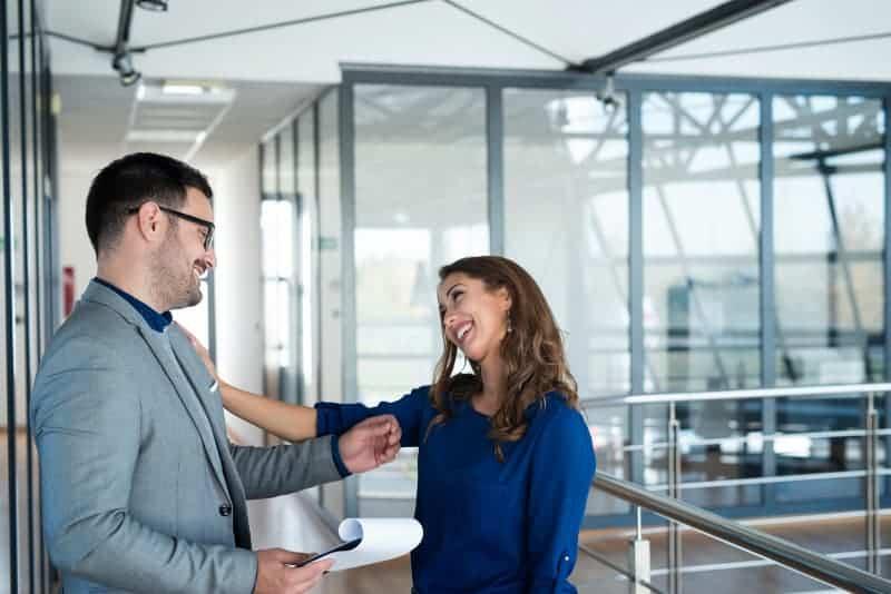 herzliches Gespräch eines Mannes und einer Frau in einer Firma
