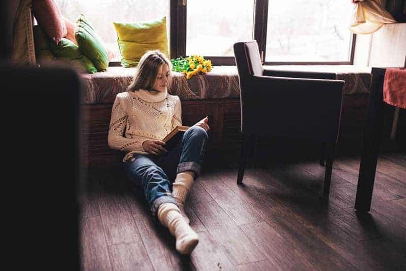 junge Frau liest ein Buch auf dem Boden