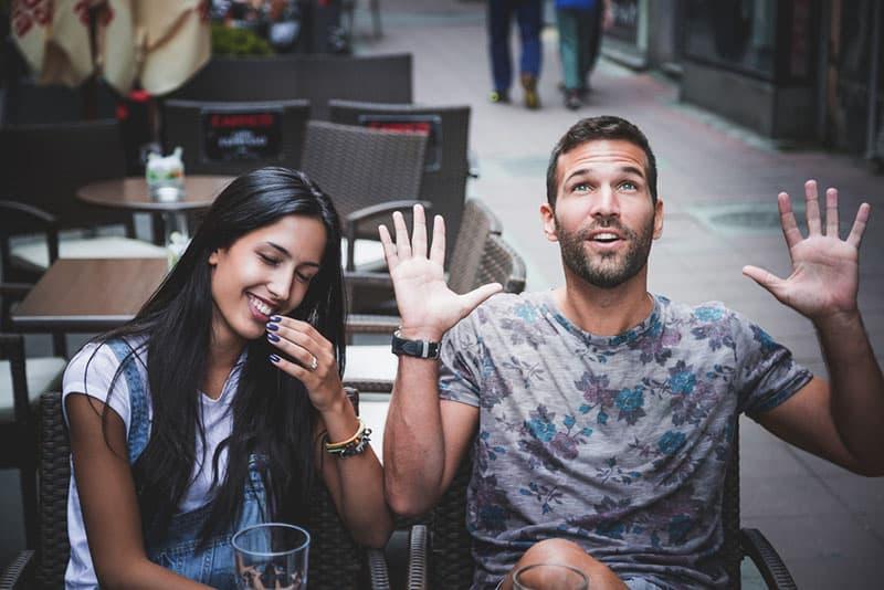 junger Mann lacht mit Mädchen im Café