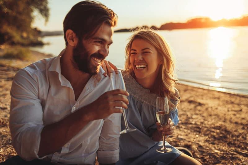 junges Paar, das Champagner am Strand trinkt
