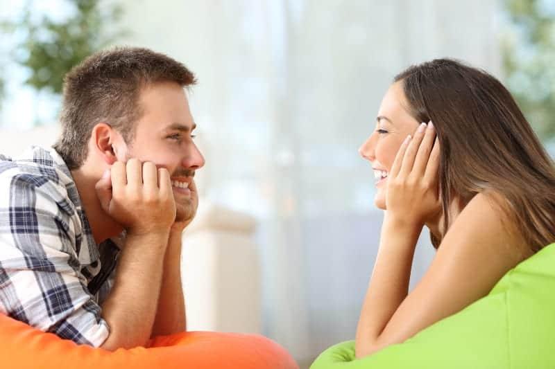 lächelndes Paar, das einander schaut, während auf Lazada-Tasche liegend