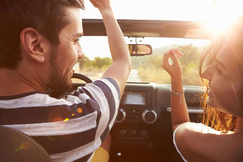lächelndes Paar, das im Auto fährt