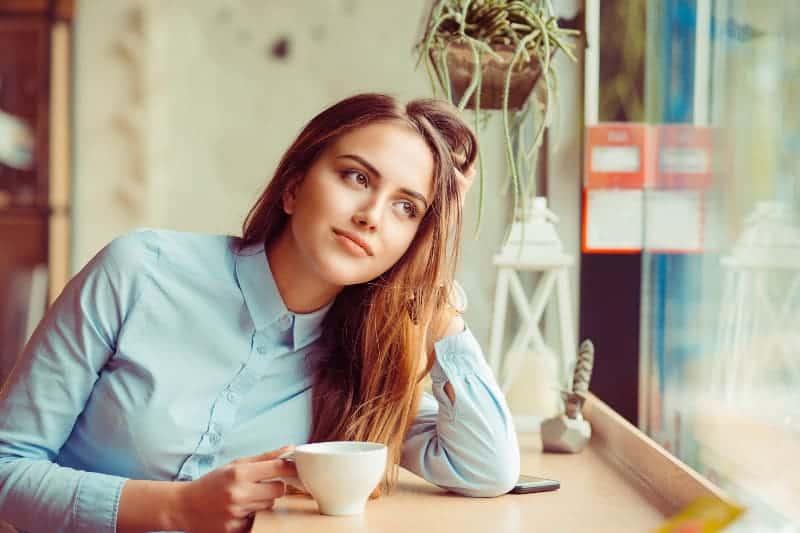 nachdenkliche Frau im Café, das durch Fenster schaut