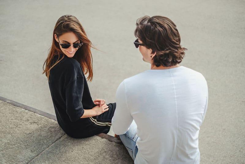 schüchterne Frau, die draußen mit Mann sitzt