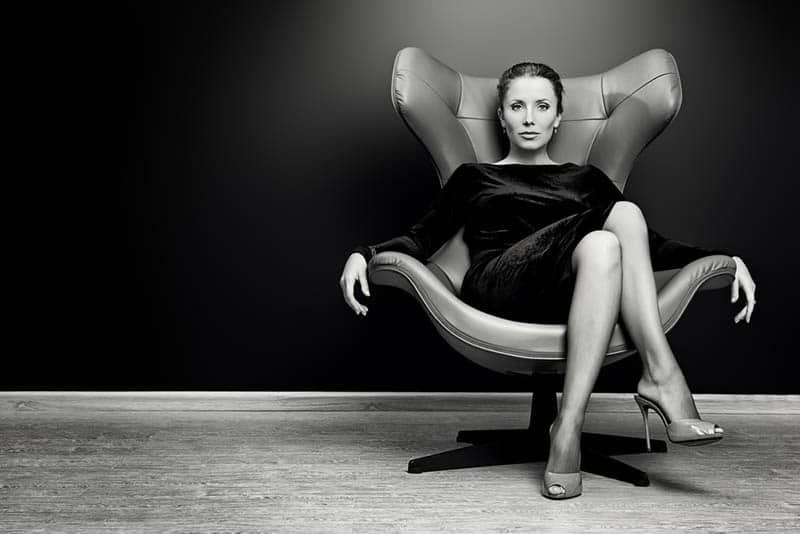 selbstbewusste ernsthafte Frau, die auf dem Stuhl aufwirft