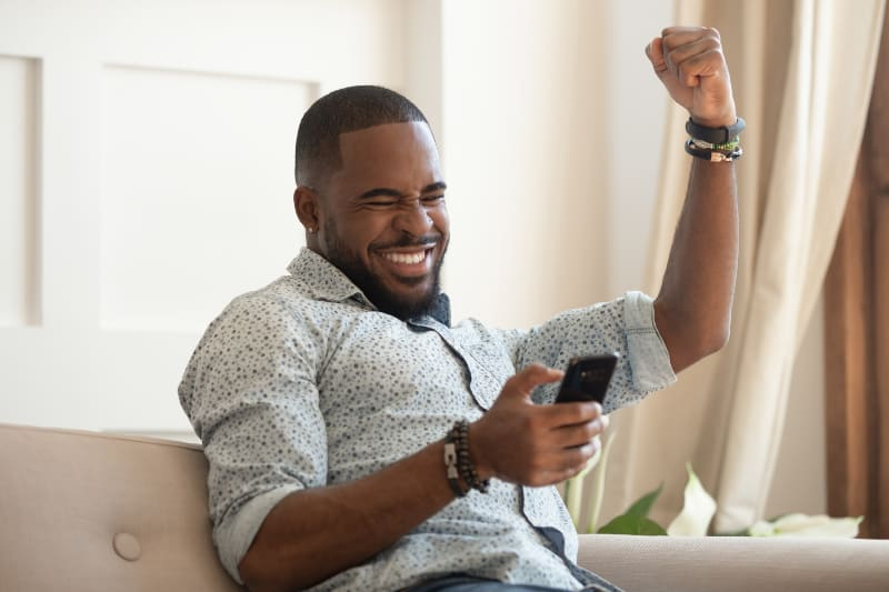 man winner holding smartphone