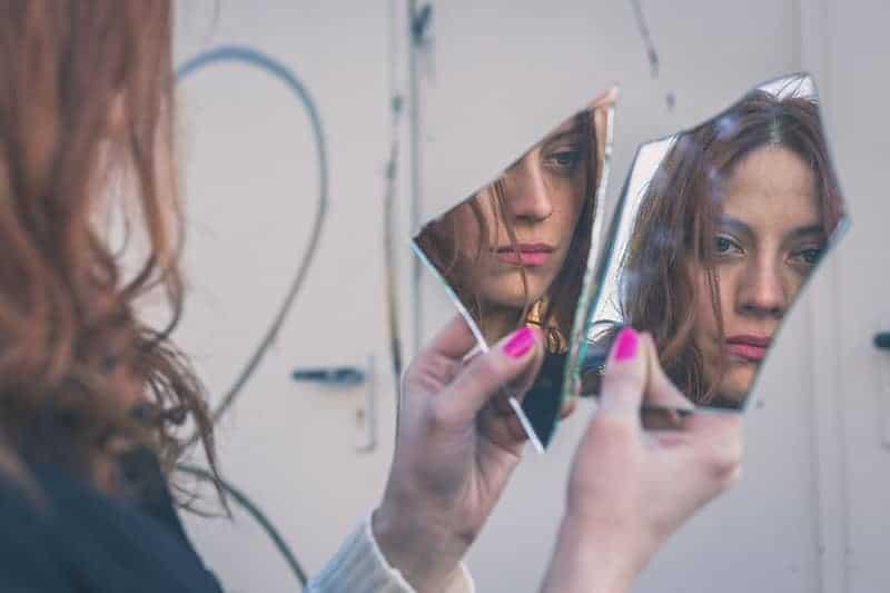 traurige Frau, die einen zerbrochenen Spiegel hält