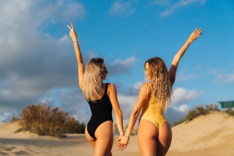zwei Freunde in Bikinis am Strand spazieren