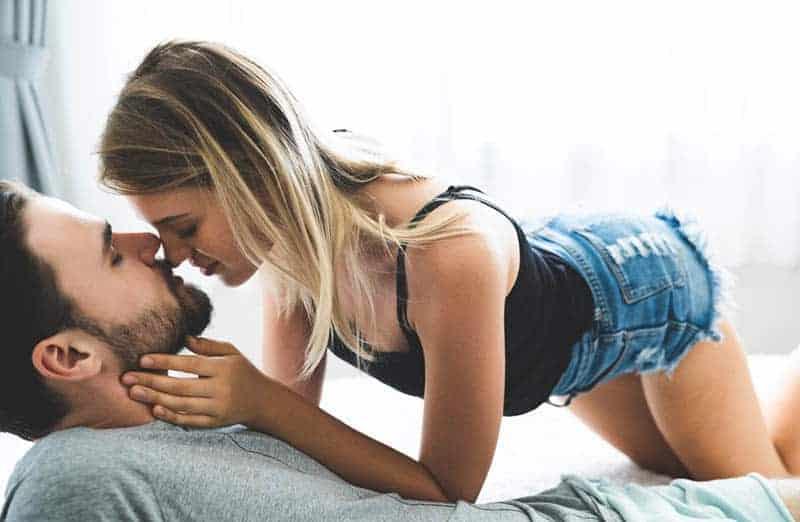 Auf dem Bett küsst eine Frau in Shorts und einem schwarzen T-Shirt einen Mann mit Bart
