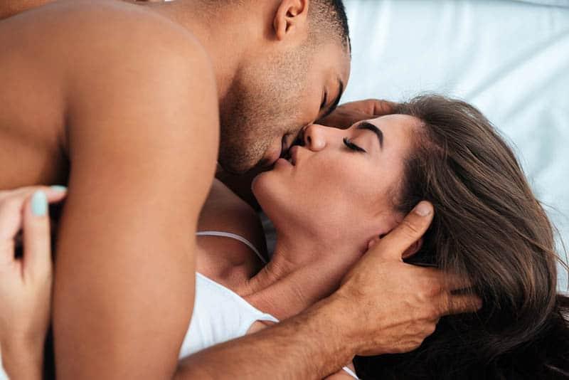 Auf dem Bett lieben sich ein Mann und eine Frau