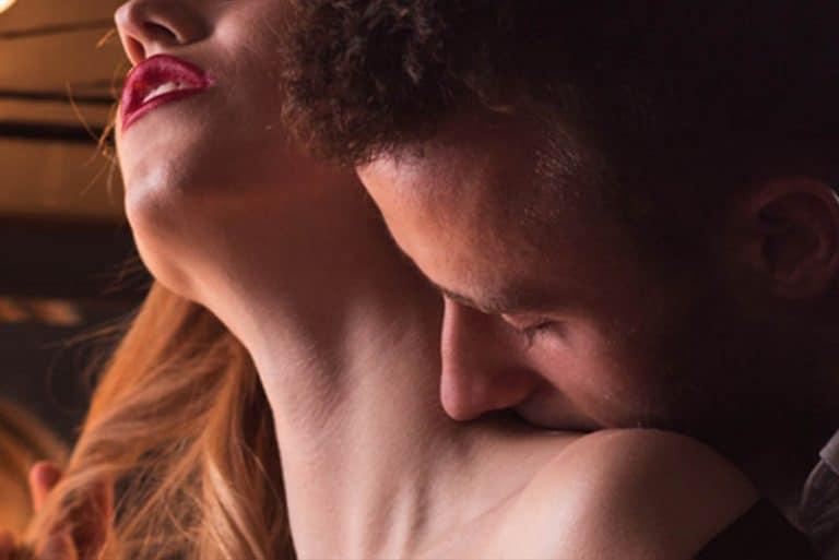 Das Mädchen genießt es, während der Mann sie auf den Hals küsst