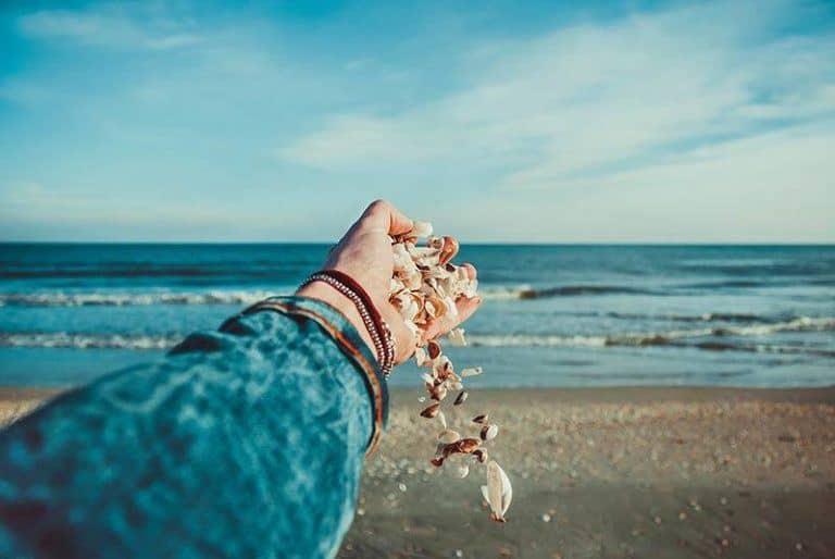 Das Mädchen lässt die Muscheln von ihrer Hand fallen