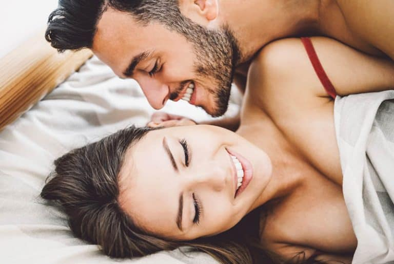 Das Mädchen lacht, als der Mann ihr ins Ohr flüstert