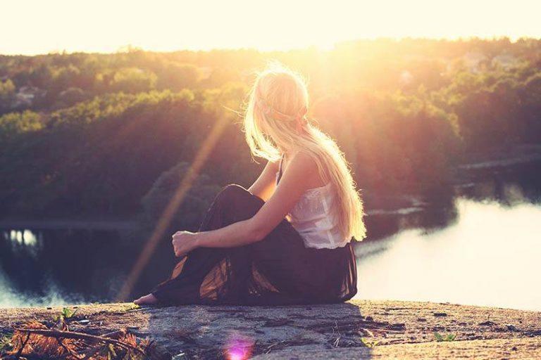 Das Mädchen sitzt auf einem Felsen, in der Sonne gebadet