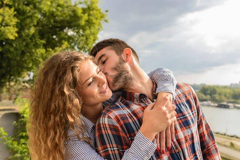Das Mädchen umarmt den Jungen, während er sie auf die Wange küsst