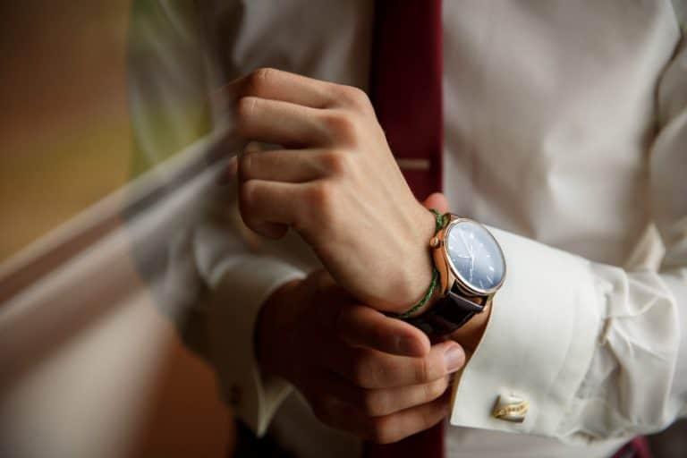 Der Mann legt eine Uhr auf seine Hand