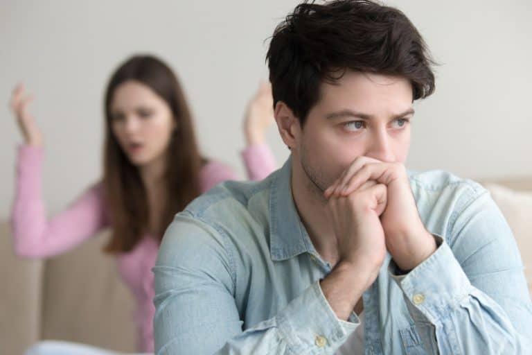 Der gehackte Mann sitzt, während seine Frau ihn anschreit