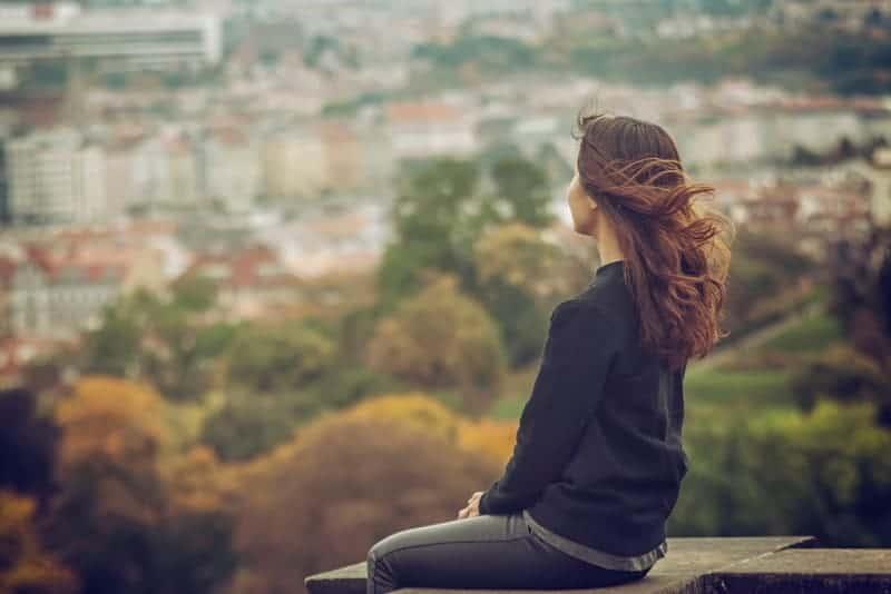 Die Frau sitzt alleine auf dem Beton und beobachtet die Stadt