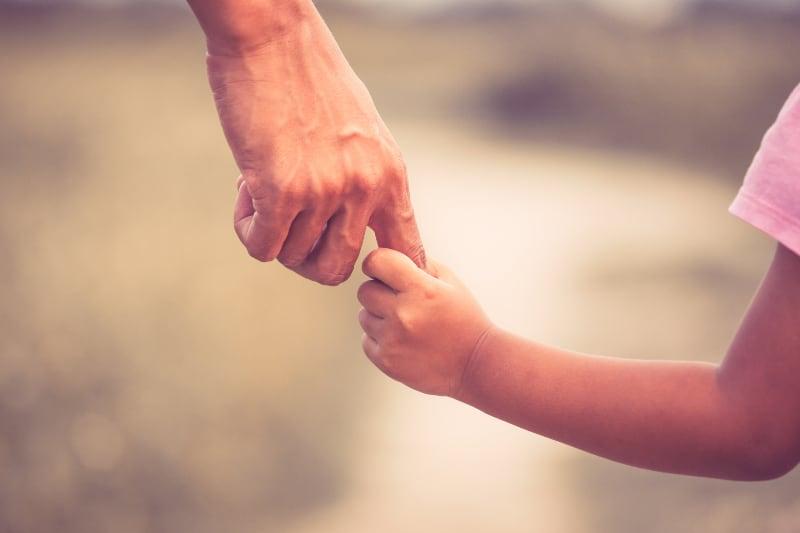 Die Hand des Kindes hält den Finger des Elternteils