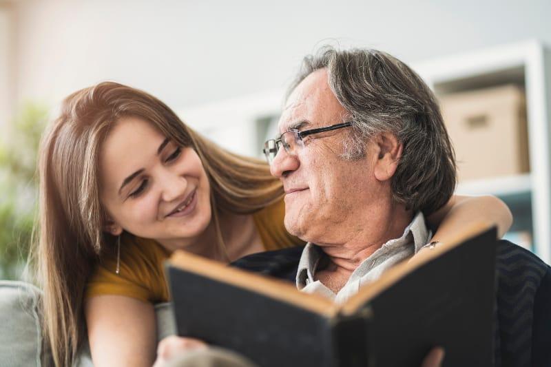 Die Tochter umarmt den Vater, der das Buch liest