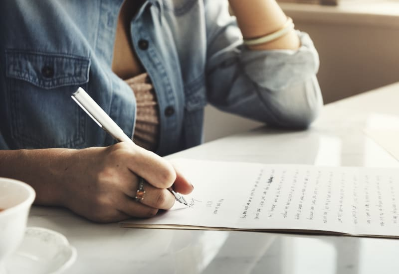 Die weibliche Hand unterschreibt einen Buchstaben