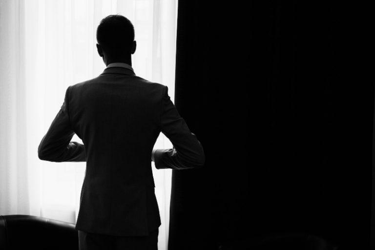 Ein Mann im Anzug schaut aus dem Fenster