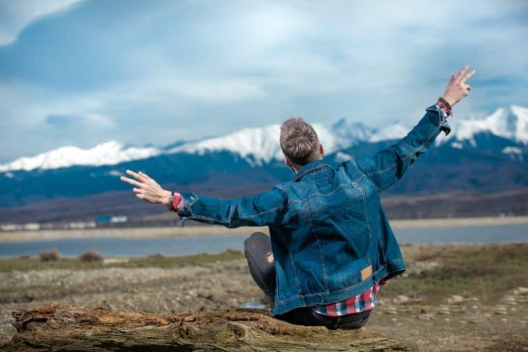 Ein Mann in einer Jeansjacke sitzt am See