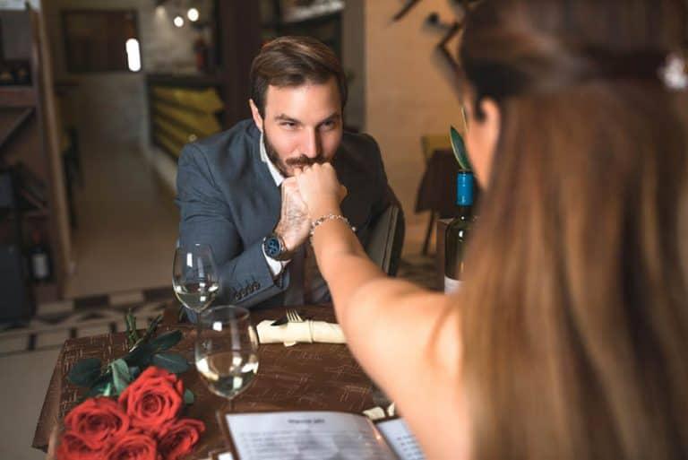Ein Mann küsst einem Mädchen bei einem romantischen Abendessen die Hand