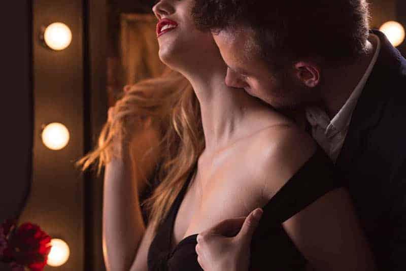 Ein Mann küsst den Hals einer geilen Blondine