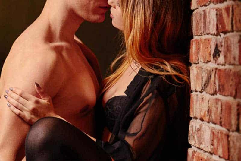 Ein Mann küsst eine Frau gegen eine Mauer