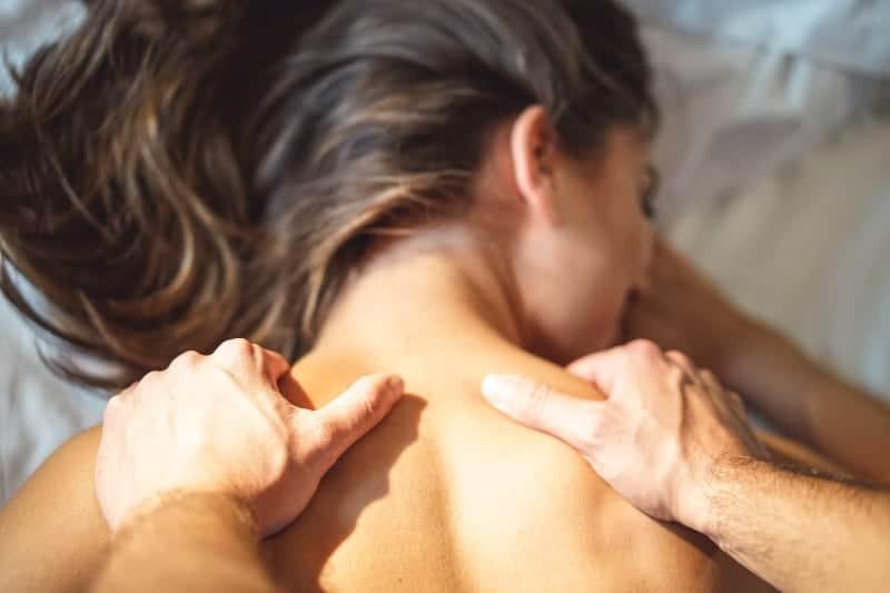 Ein Mann massiert eine Frau auf dem Bett