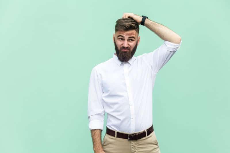 Ein Mann mit Bart kratzt sich am Kopf