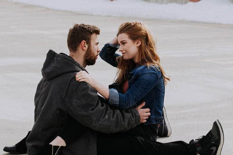 Ein Mann mit Bart und eine Frau sitzen am Strand und reden