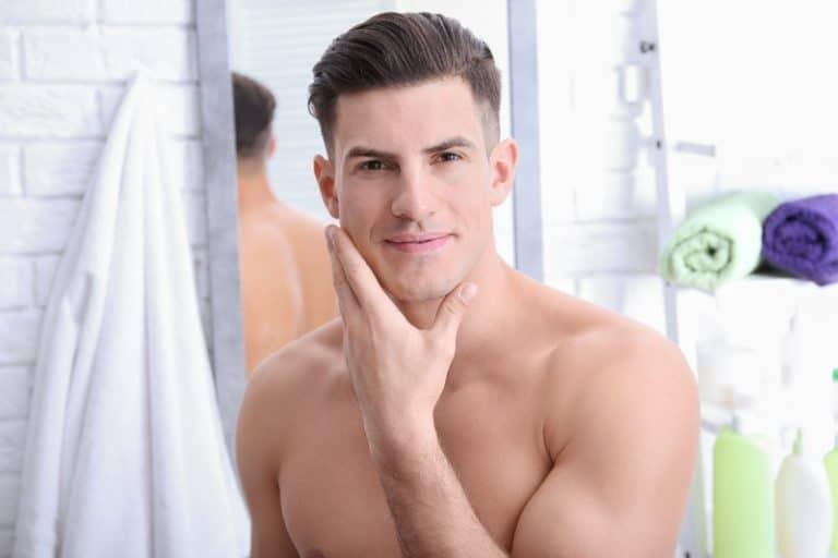 Ein Mann posiert nach der Rasur im Badezimmer