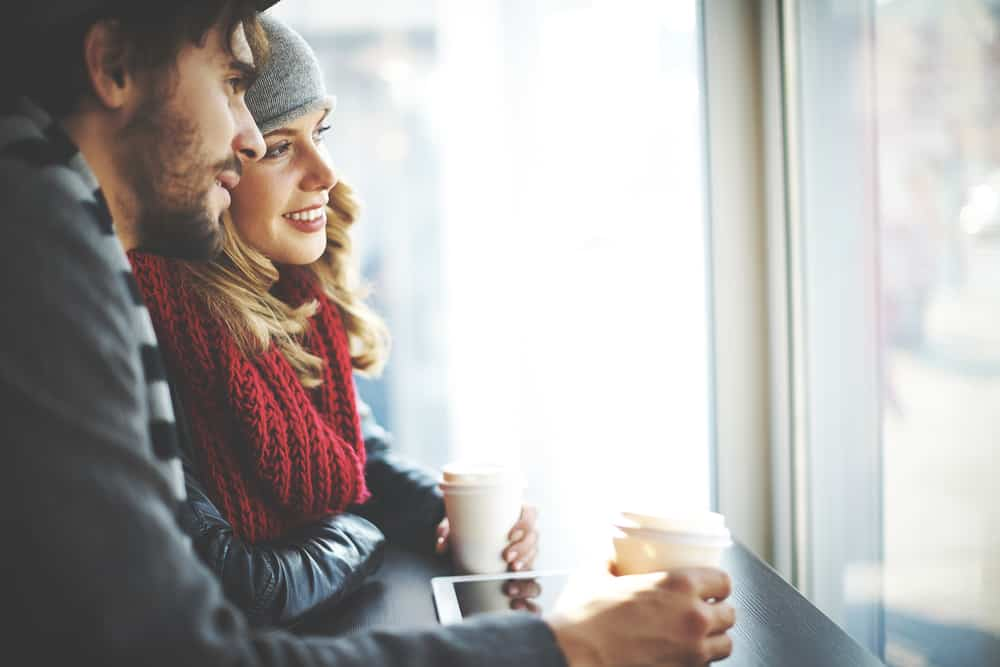 Ein Mann und eine Frau an der Bar stehen und trinken Kaffee