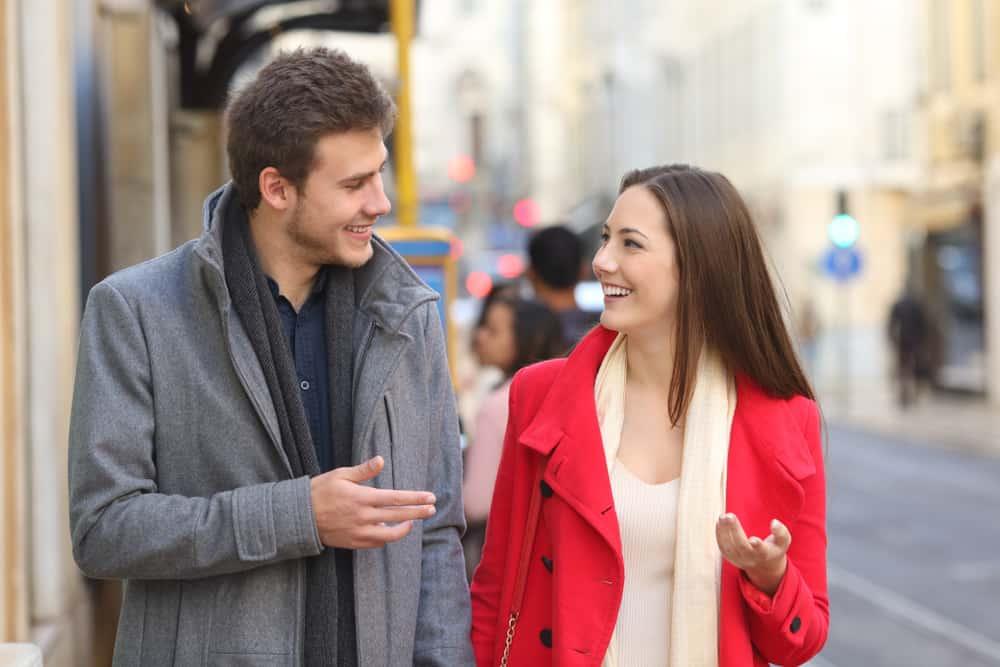 Ein Mann und eine Frau gehen die Straße entlang und unterhalten sich