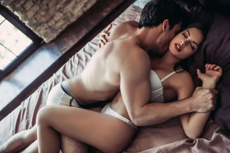 Ein Mann und eine Frau in Unterwäsche genießen sich im Bett