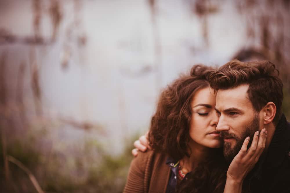 Ein Mann und eine Frau sitzen draußen und umarmen sich