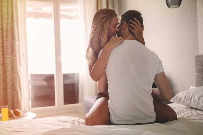 Ein Mann und eine Frau sitzen in einer Umarmung auf einem Doppelbett