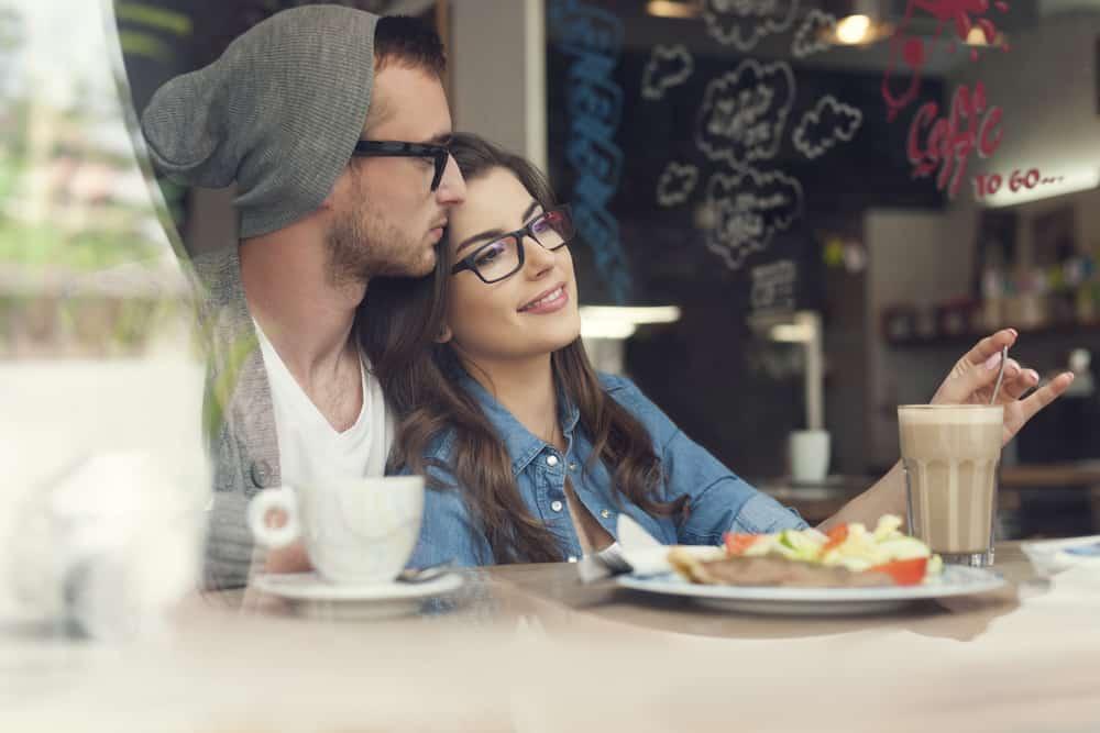 Ein Paar in einer Umarmung sitzt in einem Café und trinkt Kaffee