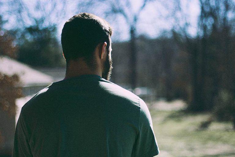Ein einsamer Mann geht durch den Wald